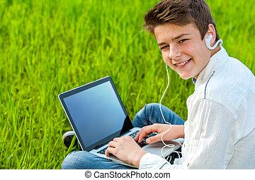 Teen working on laptop outdoors.