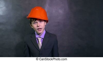 teenage angry boy architect builder in helmet swears yells dissatisfied error slow motion