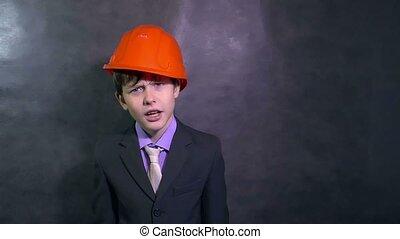 teenage angry boy architect builder in helmet swears yells...