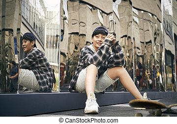 teenage asian child skateboarder relaxing on street