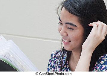 Teenage Asian girl reading a book