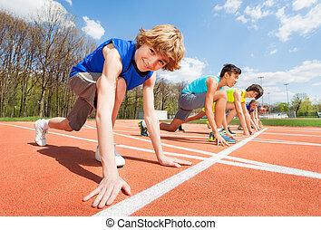 Teenage athletes preparing to start running