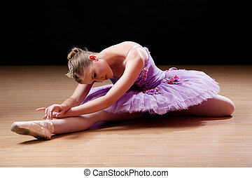 Teenage ballerina performing stretching exercises