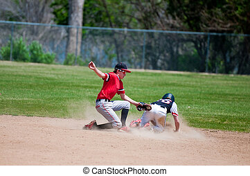 Teenage baseball shortstop tagging player out at second base...