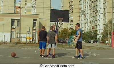Teenage basketball players shaking hands after match -...
