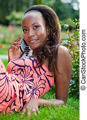 Teenage black girl using a phone, lying on the grass