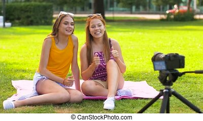 teenage bloggers recording video by camera in park -...