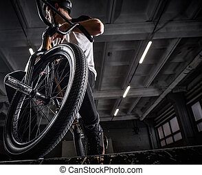 Teenage BMX rider sitting on his bicycle in a skatepark indoors
