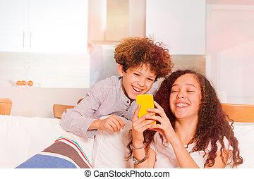 Teenage boy and girl having fun surfing internet