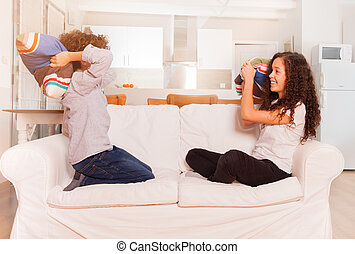Teenage boy and girl pillow fighting on the couch