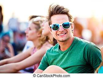Hipster teenage boy in green t-shirt and sunglasses with his friends at summer music festival, sitting on the ground