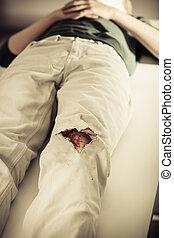 Teenage boy awaiting triage at a hospital lying on a gurney...