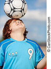 boy balancing soccer ball on his head