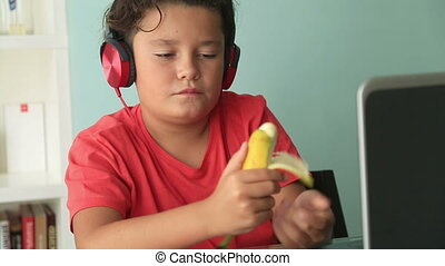 Teenage boy eating banana