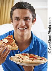 Teenage Boy Eating Pizza At Home