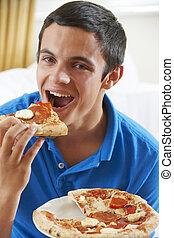 Teenage Boy Eating Slice Of Pizza