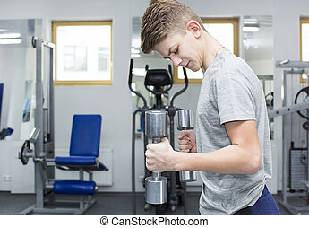 Teenage boy engaged in the gym hall