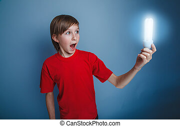 teenage boy European appearance in red shirt holding burning...