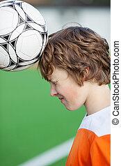 teenage boy heading the ball at soccer