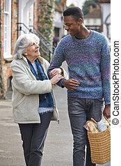 Teenage Boy Helping Senior Woman To Carry Shopping