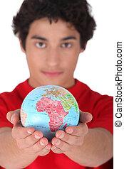 Teenage boy holding a mini-globe