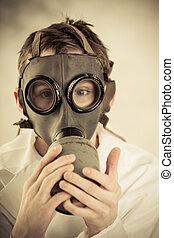 Teenage boy holding gas mask on face