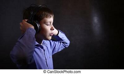 Teenage boy in a blue shirt in big headphones listening to music dark background video