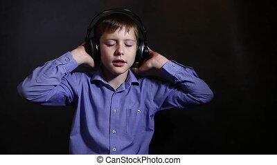 Teenage boy in a blue shirt in big headphones listening to...