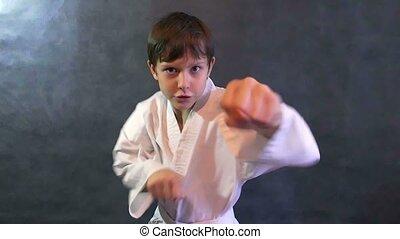 teenage boy in a kimono karate fight hands waving fists slow motion