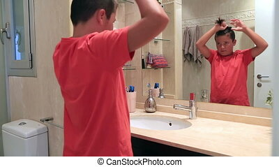 Teenage boy in front of the mirror brushing his hair