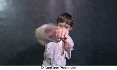 teenage boy in kimono fight hands karate waving fists slow motion