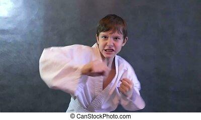teenage boy in kimono fight karate hands waving fists slow motion