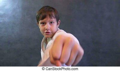 teenage boy in kimono karate fight hands waving fists slow motion