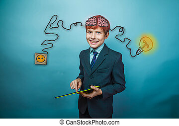 Teenage boy in suit smiling and working in the tablet charging cord plug wire igniter charge and sketch infographics