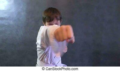 teenage boy karate in kimono fight hands waving fists slow motion