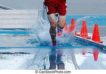 Teenage boy lands in water during a steeplechase race