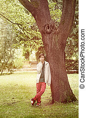 teenage boy leaning against a tree in a park