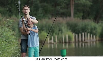 Teenage boy learning to fish with father's help - Teenager...