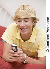 Teenage Boy Lying On Bed Using Mobile Phone