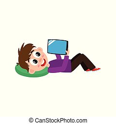 Teenage boy lying on his back with tablet computer