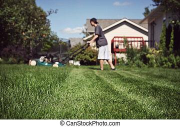 Teenage boy mowing lawn