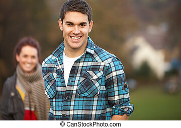 Teenage Boy Outside With Girlfriend In Background
