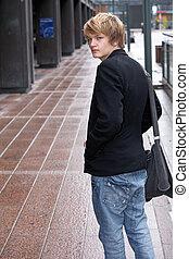 Teenage Boy - Teenage boy looking back over his shoulder in...