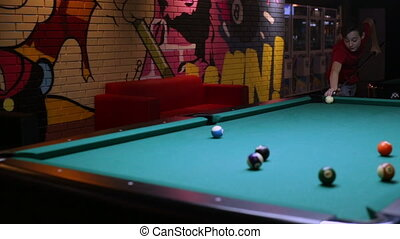 Teenage boy play pool, sending ball in the hole
