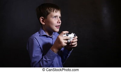 Teenage boy playing a video game console is holding a...