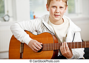 Teenage boy playing guitar