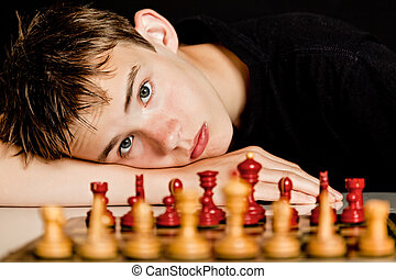 Teenage Boy Resting Head on Table Near Chess Board