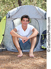 Teenage boy sitting in front of his tent on a sunny day
