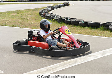 Teenage boy sitting in go-kart at an outdoor track