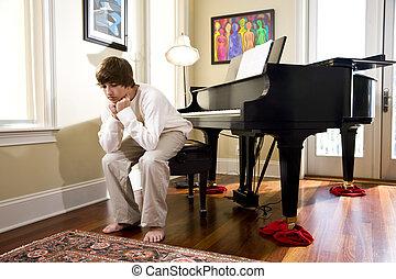 Teenage boy sitting on piano bench looking down